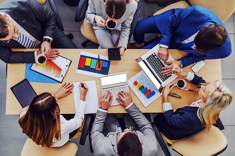 Konferenztisch mit fünf Personen in Business-Kleidung